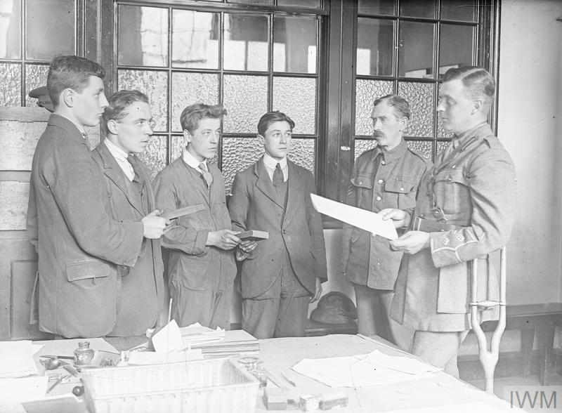As an army officer reads out the oath, four young men hold Bibles and confirm their allegiance at a recruitment office. Taken at Treaty Lodge, Hounslow, the HQ of the 8th Battalion, Middlesex Regiment, in September 1917.
