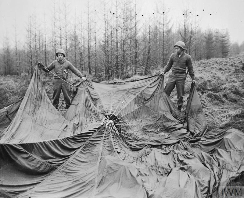 The German Counter Offensive 16-22 December 1944: Two American soldiers, Thomas Richardson and G Leach, examining a German parachute found in the forest. The Germans hoped to spread confusion by infiltrating small groups of specially-trained English speaking troops with captured uniform and equipment to perform sabotage and intelligence missions.