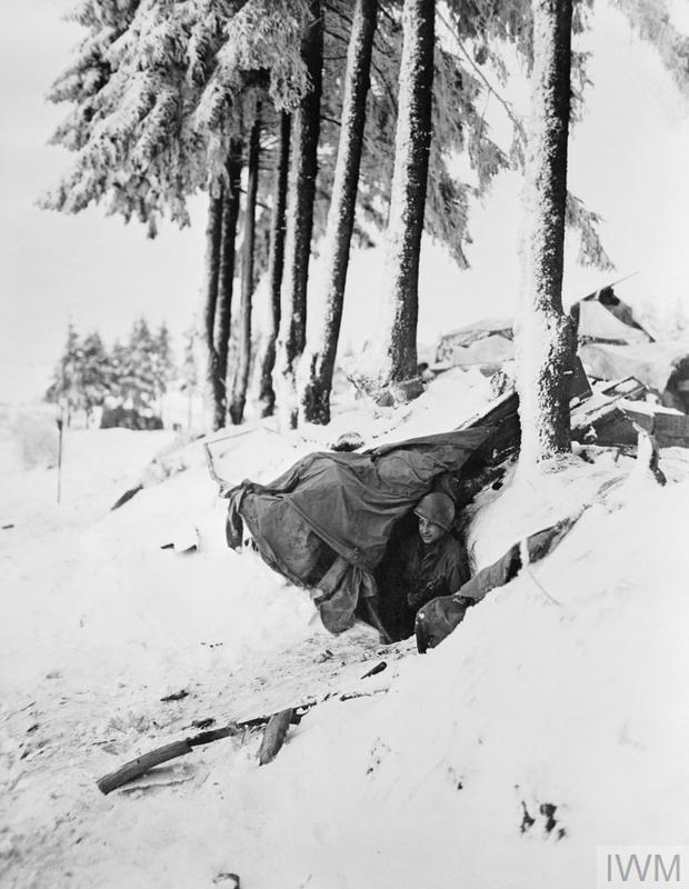Sergeant John Opanowski of the 10th Armoured Division, emerges from a dug-out built under snow in the Bastogne area. The 10th Armoured Division and the 101st Airborne Division were pinned down in the Bastogne area by General von Manteuffel's crack Panzer Divisions - the 2nd and the 116th.