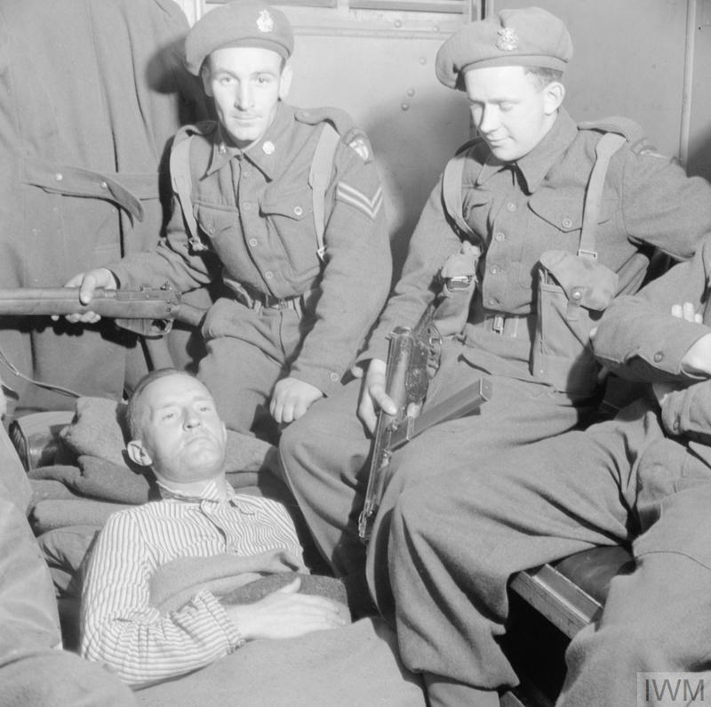 Fascist politician and Nazi propaganda broadcaster William Joyce, known as Lord Haw Haw, lies in an ambulance after his arrest by British officers at Flensburg, Germany, on 29 May 1945. He was shot during the arrest.