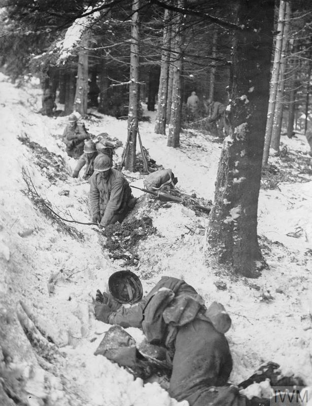 The Allied Counter Attack 25 December 1944 - 28 January 1945: American soldiers dig hasty foxholes in snow covered terrain as enemy fire opens up near Berismenil. A dead soldier lies in the foreground.