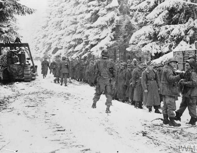 The Allied Counter Attack 25 December 1944 - 28 January 1945: Germans captured by troops of the 82nd Airborne Division are lined up at the side of a snowy road near Hierlot, Belgium.