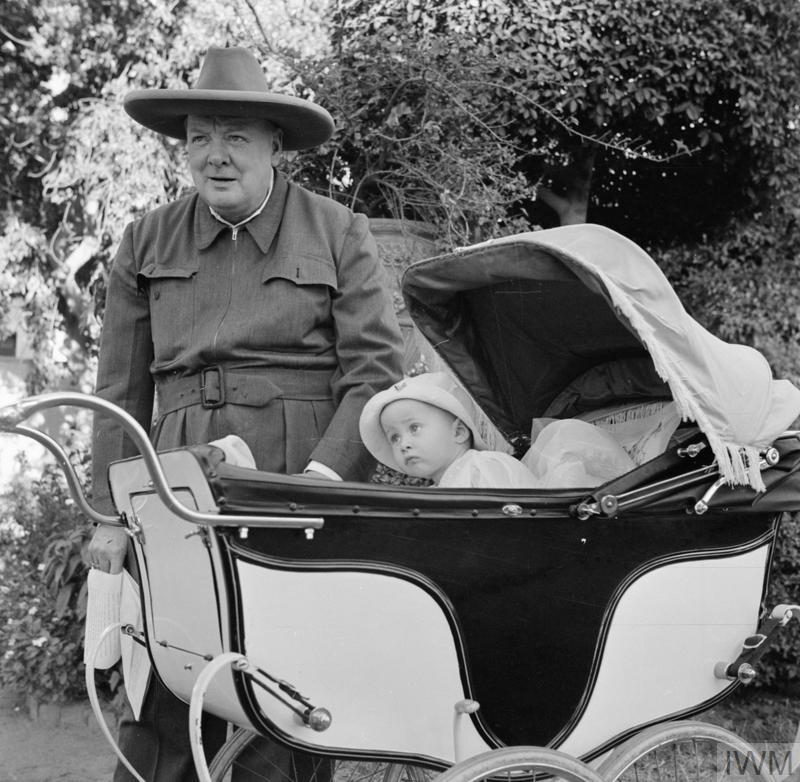 The Prime Minister Winston Churchill, wearing his world famous siren suit, with Victor Lampson, the young son of His Excellency the Honourable Sir Miles Lampson, the British Ambassador, and Lady Lampson, in the gardens of the British Embassy, Cairo, Egypt on 8 August 1942.