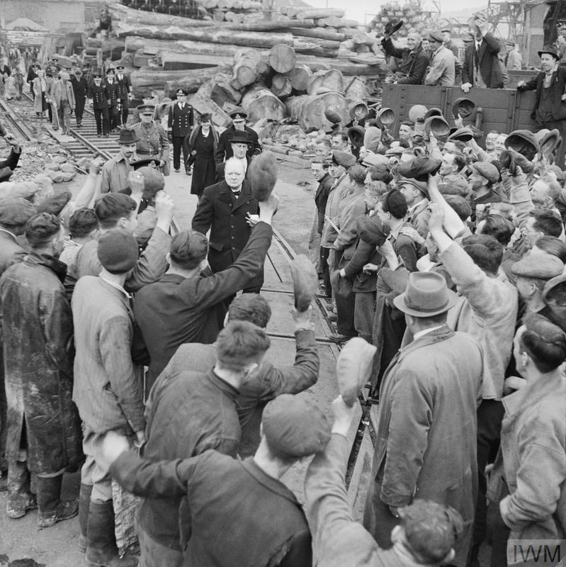 Winston Churchill is cheered by workers during a visit to bomb damaged Plymouth on 2 May 1941. The Prime Minister was accompanied by Lady Nancy Astor, Lord Mayoress of Plymouth, on this visit, who can be seen behind Churchill.