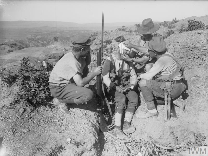 Australian soldiers dressing the head wound of an injured comrade with his first aid field dressing.