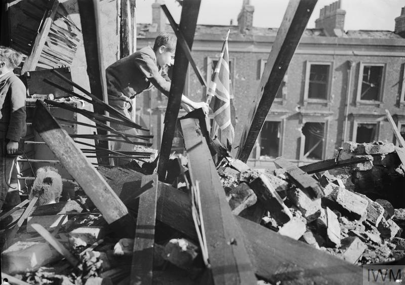 A young boy places a Union flag into the remains of his home, which was destroyed in an air raid on London in 1940.