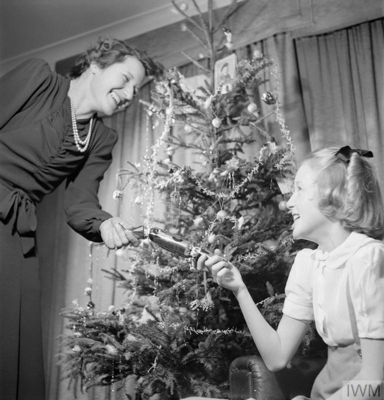 Mrs Devereux and her daughter Jean pull a Christmas cracker in front of their Christmas tree, bought under the YMCA scheme.