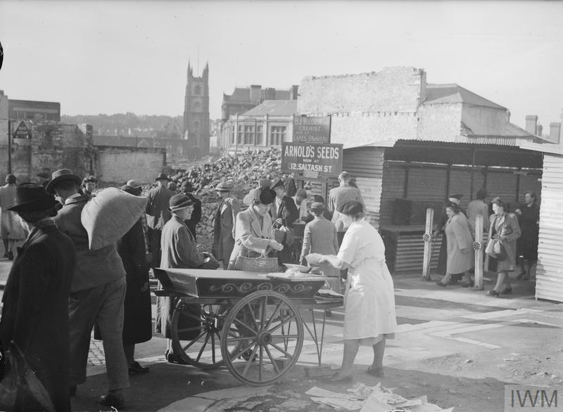 Men and women shop at a stall and in corrugated iron sheds which have been erected in place of shops that were destroyed during an air raid. Amid the rubble, signs advertising the new locations of various shops state that B J Woodrow, Chemist and Arnold's Seeds have moved to Market Avenue and Saltash Street respectively.