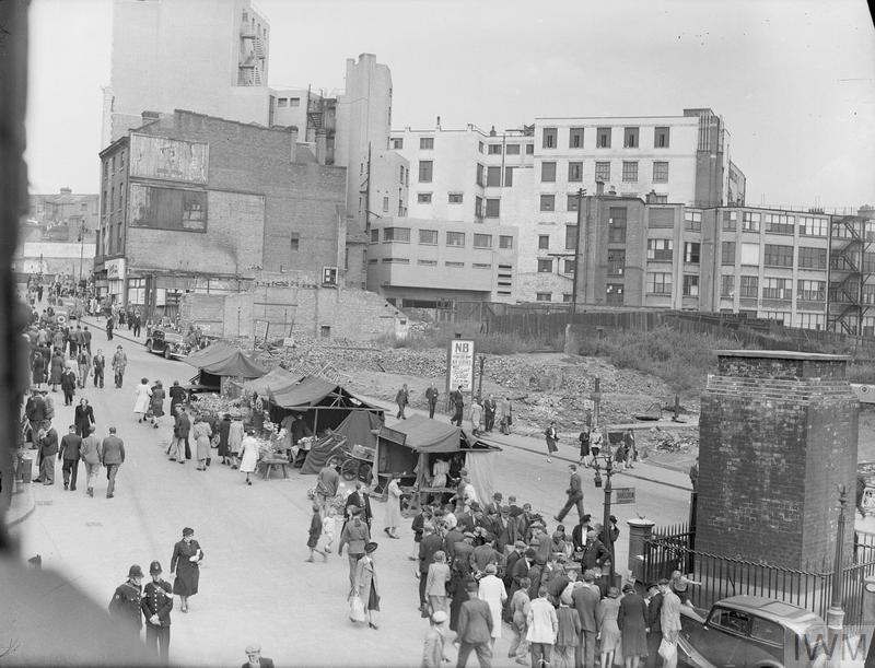 Men and women shop amongst the market stalls that line the centre of the road in Birmingham's bomb-damaged Bull Ring Market Square. Rubble and the exterior walls, which can be seen in the background of the photograph, are all that remains of the old market.