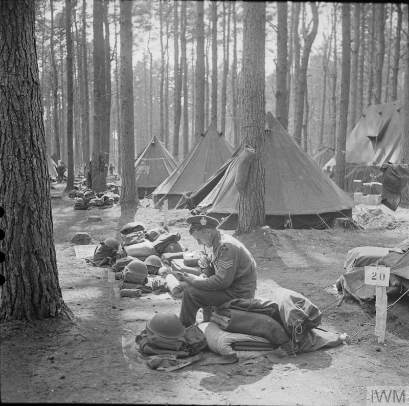 Sergeant Ernest Docherty of the 1st Battalion King's Own Scottish Borderers, part of 3rd Infantry Division, composes a letter from his unit's tented camp at Denmead in Hampshire, 29 April 1944.