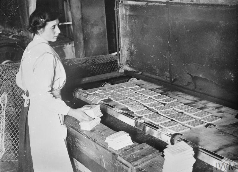 A female worker in a Lancashire biscuit factory baking army biscuits in a rotating oven.