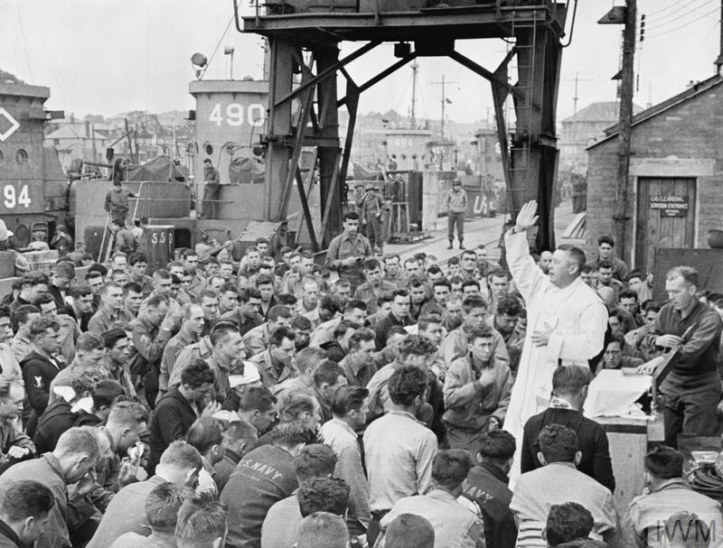 Father (Major) Edward J Waters, a US Army Catholic chaplain, conducts a service on the quayside at Weymouth for army and navy personnel about to take part in the invasion of Europe, June 1944. Troops from Weymouth were destined for Omaha assault area.