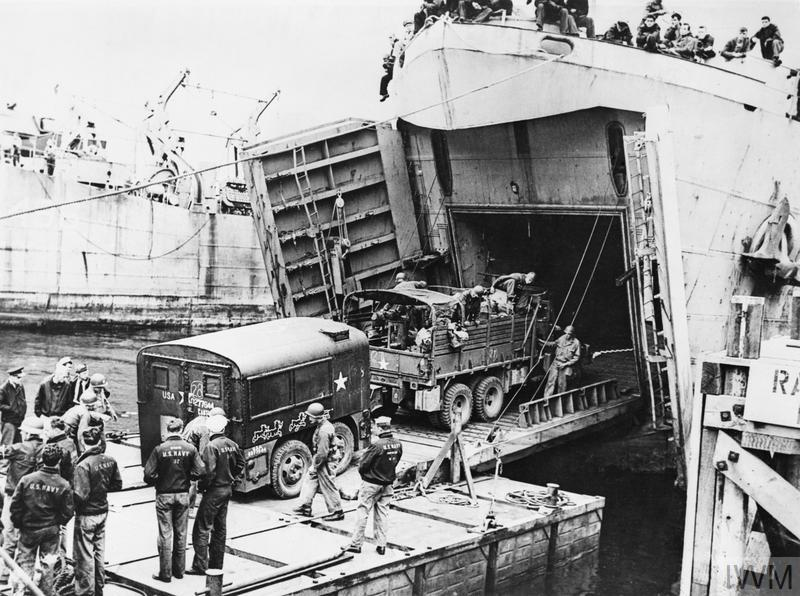 A US truck towing a field kitchen drives aboard an LST (Landing Ship Tank) at Brixham in Devon during preparations for the invasion of Europe, June 1944.
