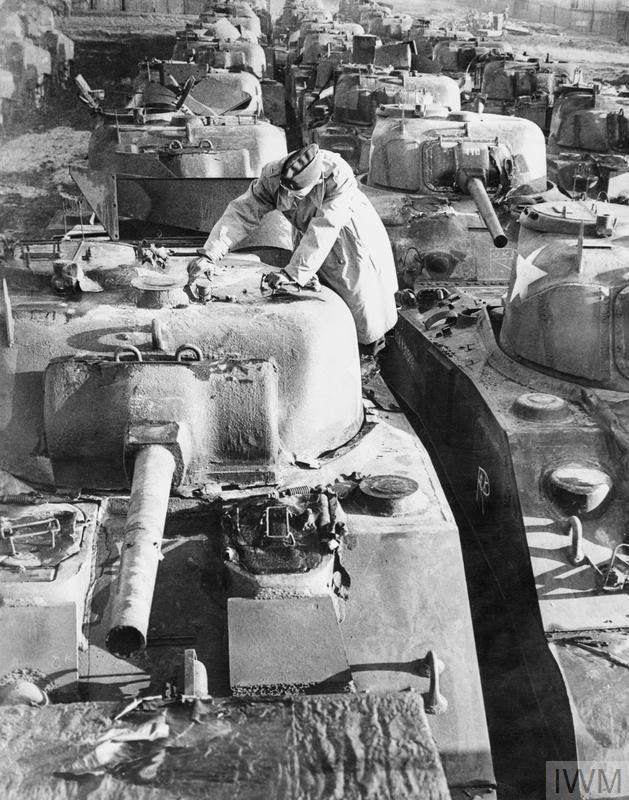 A US officer checks a line-up of newly delivered M4 Sherman tanks at a supply depot in Britain, 1944.