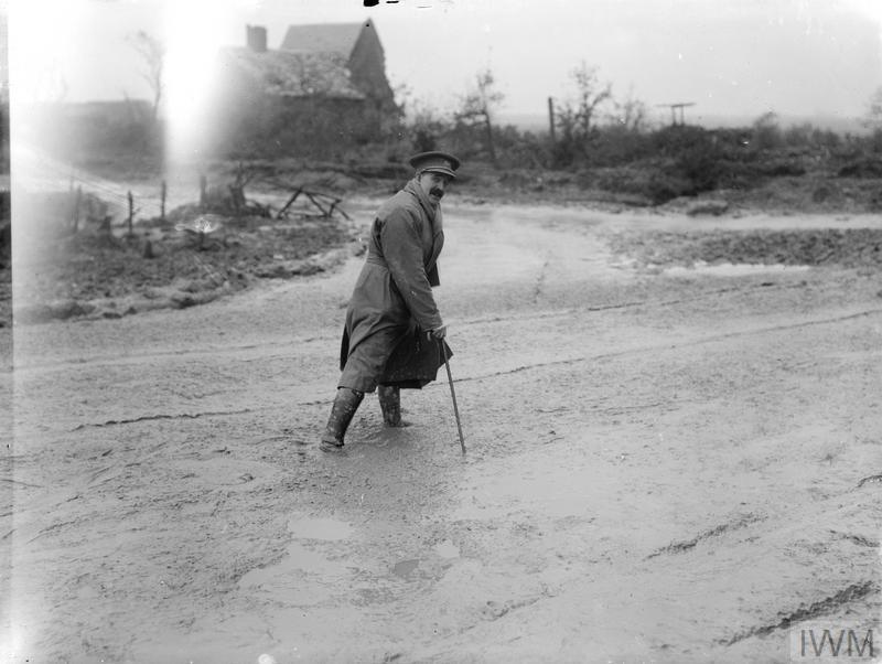 The war artist Lieutenant Muirhead Bone crossing a muddy road, Maricourt, September 1916.