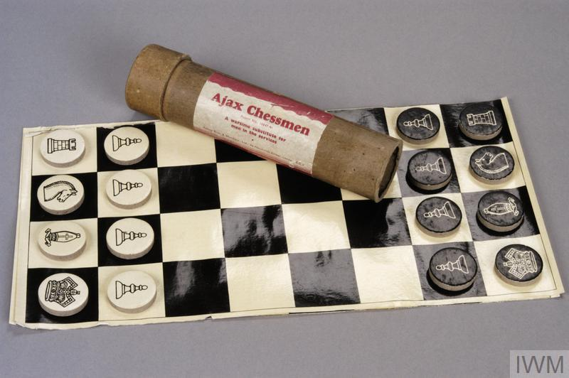 "Ajax chess set made by Adams Brothers & Shardlow Ltd. consisting of: A cardboard tube with separate lid. A paper label is pasted onto the tube that reads ""Ajax Chessmen A wartime substitute for men in the services"". 2 rolled chess board sections, presumably designed to be pasted onto a board."