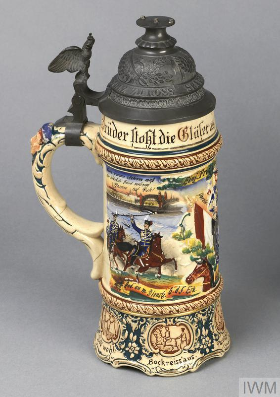 Porcelain bierstein (H 30cm x diameter 11cm) with metal lid. The piece is decorated with 'cavalry scenes' and the following ornate inscriptions: 'Brueder stokt die Glaeser an hoch lebe der Reservemann'-(around edge just under rim) / 'Stolz zu Ross; Spaet & Frueh; Die Cavallerie' (on lid) / 'Wenn Husaren attakieren muss der staerkste Feind verlieren; Reserve had Ruh!'