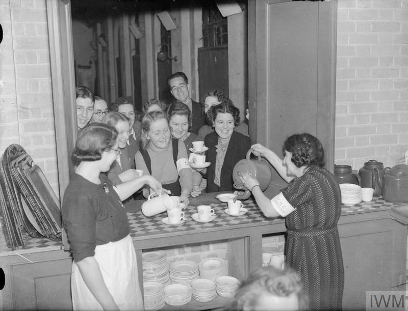 Workers in the John Keble Church kitchen supply tea to other shelter volunteers to be distributed to shelterers. The lady pouring the tea wears a 'JKC SUPERVISOR' armband, whilst the teenage girl collecting a cup of tea wears a 'JKC STAFF' armband.