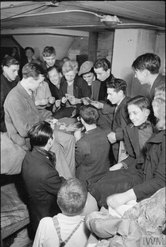A group of local boys play a game of cards in this air raid shelter, probably a basement shelter, somewhere in South East London, in November 1940.