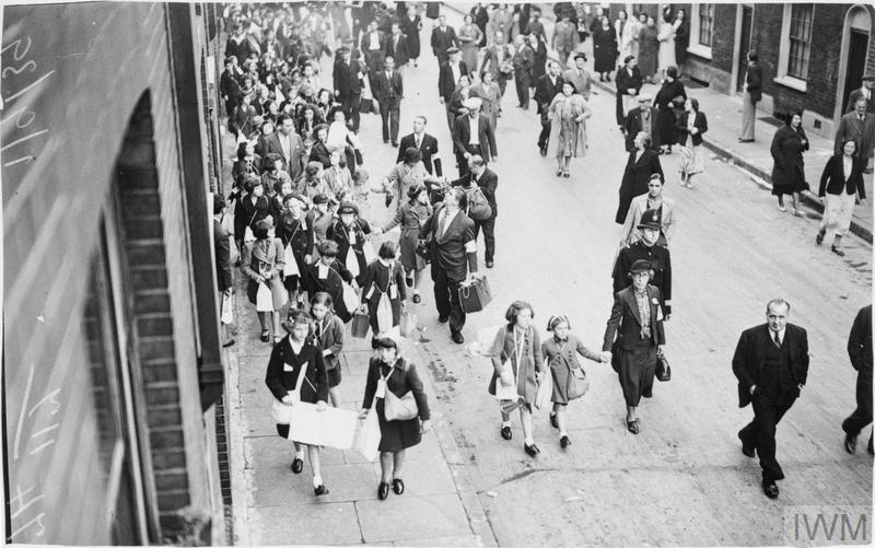 An early start to evacuation is made by children of Myrdle School in Stepney. The children assembled at school at 5am on Friday 1 September 1939. This photograph shows evacuees and adults walking along a street carrying suitcases and gas mask boxes. The adults are wearing arm bands which identify them as volunteer marshals.