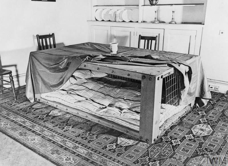 A photograph of a Morrison shelter in a room setting, showing how such a shelter could be used as a table during the day and as a bed at night. The table cloth is partly pulled back to reveal the sleeping area.