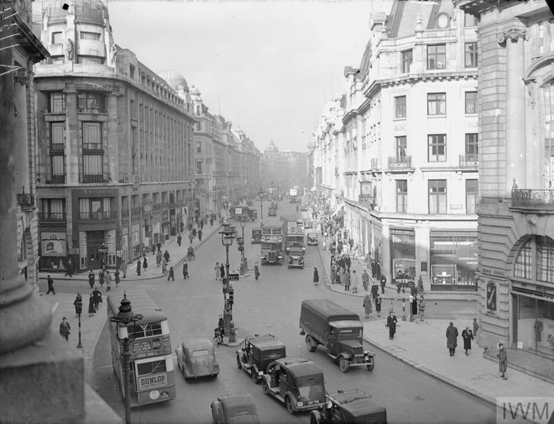 A wide view of Regent Street showing buses, cars and pedestrians going about their daily business. A large shop, R W Forsyth, can be seen on the left of the photograph at the crossroads where Vigo Street (on the left) and Glasshouse Street (on the right) join Regent Street. It is interesting to note that the street lamps are empty of bulbs, as part of blackout procedures, and in the centre of the road, a sign directs people to a First Aid Post.