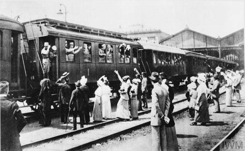 Civilians waving farewell to Austro-Hungarian troops on board trains about to depart for war service.