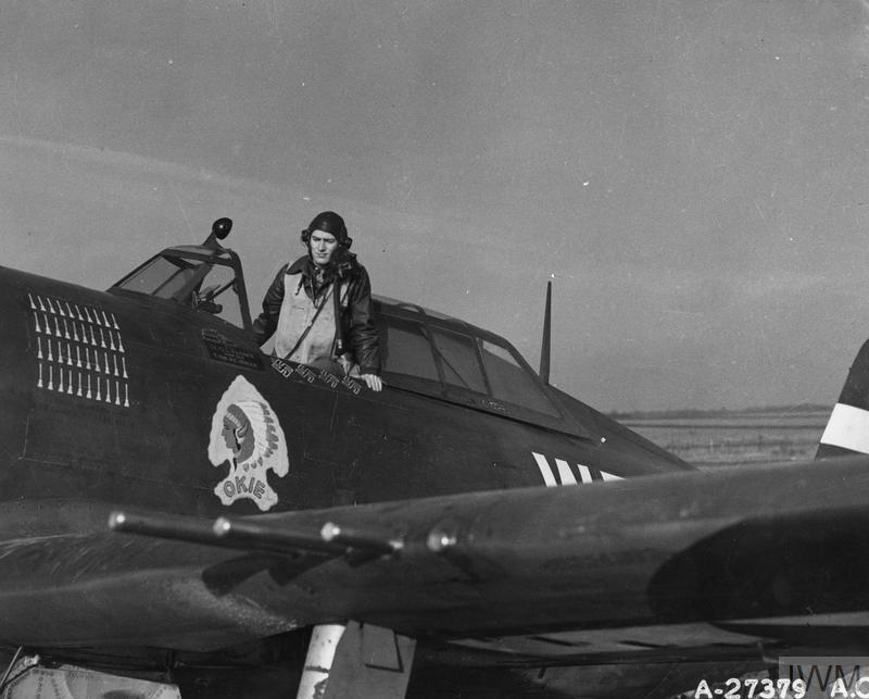 """© IWM [FRE 2977] - Lieutenant Quince Brown, of the 84th Fighter Squadron, in the cockpit of his P-47 Thunderbolt nicknamed """"Okie""""."""