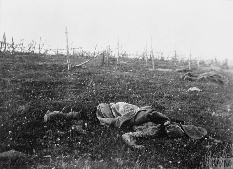 An unknown Russian soldier lying dead on the battlefield. Note lines of barbed wire in the background.