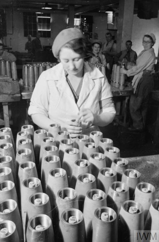 A female factory worker fits exploders into rows of shells at this filling factory. Behind her, other munitions workers can also be seen.