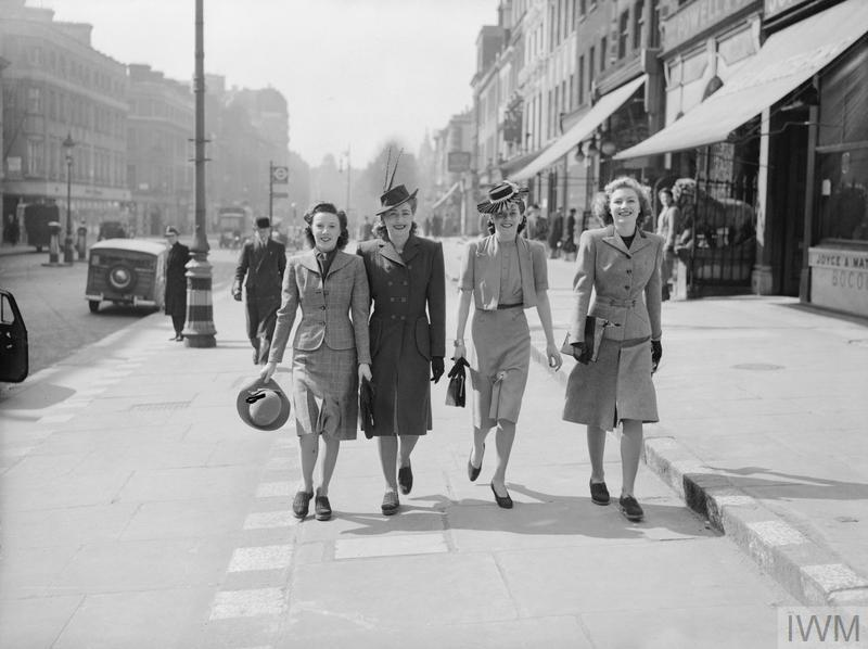 Four young ladies enjoy a stroll in the Spring sunshine along a shopping street in the West End of London. Two are wearing fancy hats, proving that wartime clothing doesn't have to be drab! Cars and other pedestrians go about their daily business behind them.