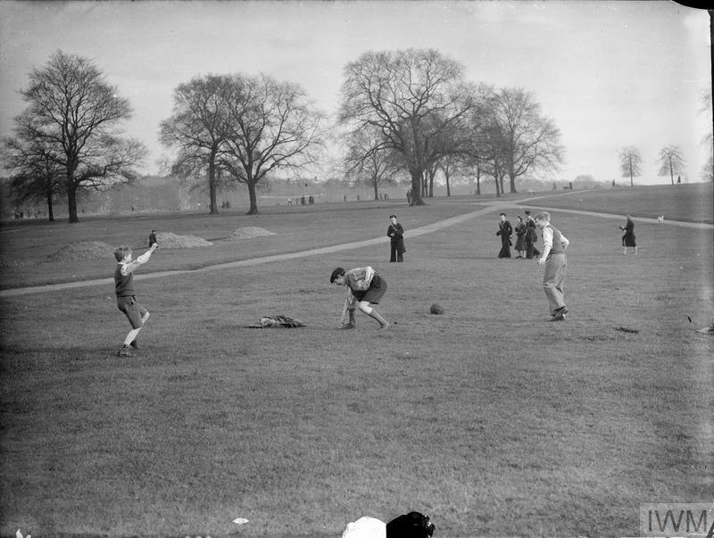 Boys, including a Boy Scout, enjoy a game of football in the sunshine in Hyde Park. A naval cadet and several other children can be seen in the background, watching from a distance.