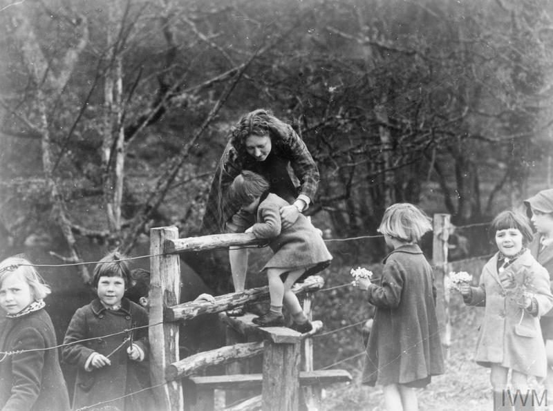 Teacher Miss Betty Hall helps three-year-old Marion Davison, the youngest evacuee to Dartington Hall, over a stile as part of their nature walk in the countryside surrounding the Dartington estate. Other evacuees can be seen in the photograph, many are holding small bunches of flowers, which they have picked along the way.