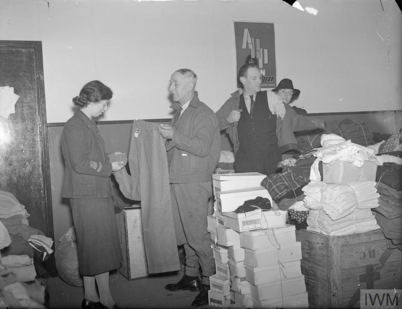 In another part of East Ham Town Hall, women of the Women's Voluntary Service (WVS) control the free issue of clothing to bombed-out citizens. Here one WVS member can be seen helping a man on with a new jacket (it appears that it was once an army tunic), and a second WVS member helps another man with a new pair of trousers. In the foreground, can be seen a pile of shoeboxes, and a crate stamped with the letters RC and a cross can also be seen.