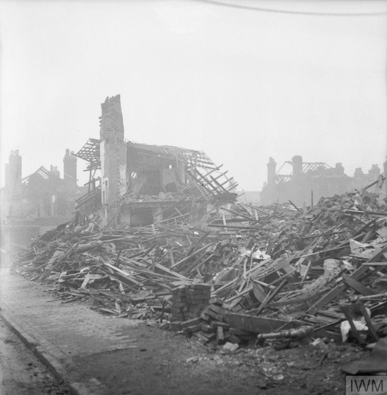Only one very badly damaged house still stands amidst the huge piles of timber and rubble following an air raid on Queen's Road, Aston, Birmingham. This site was damaged during the longest raid sustained by Birmingham, lasting 13 hours, which occurred on 11 December 1940. A few other houses can be seen in the background: all are without a roof.
