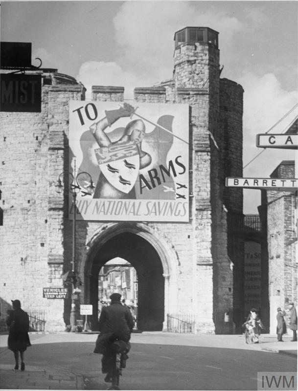 A view of the 30ft high National Savings poster produced by students of the Sydney Cooper School of Art on display on West Gate, Canterbury, during War Weapons Week. The poster depicts St. George with sword and shield, and features the words 'To Arms: Buy National Savings'. A man on a bicycle can be seen in the foreground of the photograph.