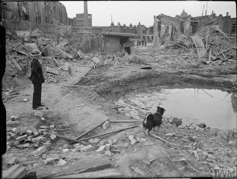 'Rip' the dog and an ARP Warden survey the scene of devastation following an air raid in Latham Street, Poplar. The bomb crater is full of water. In the background, the remains of the local surface shelter can be seen, which, although slightly damaged, is still largely intact. Piles of rubble and timber can also be seen.