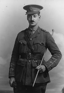 Three-quarter length photo portray of a moustached man in military uniform.  The cap and collar badges are the flaming grenade of the Royal Fusiliers