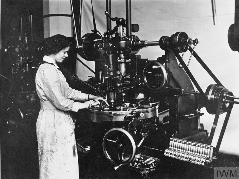 A female worker operating a vertical profiling machine, profiling the outside figure of a trigger-guard for a Lewis light machine gun.