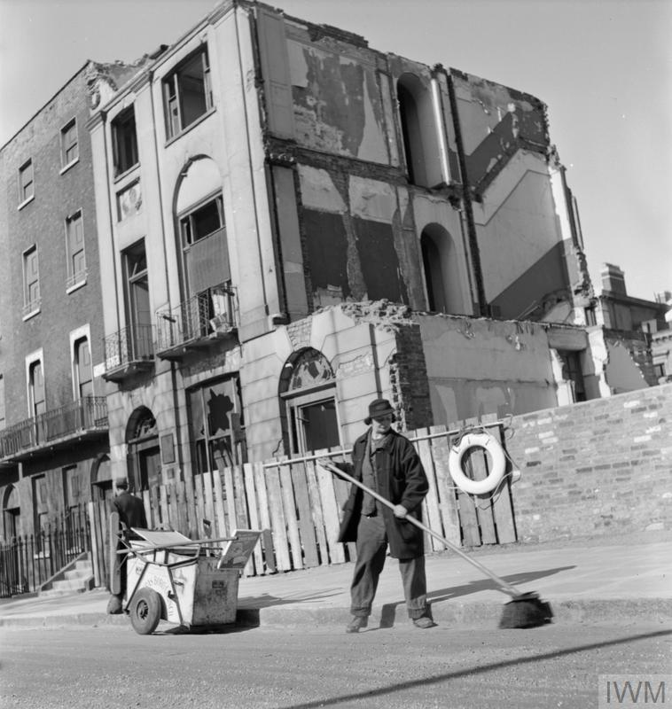 Mrs G Warren of the St Pancras Women's Street Cleaning Brigade uses a large broom to sweep the road. She is brushing in the gutter beside the kerb, with her dustcart nearby. The buildings behind her show signs of being badly damaged by air raids. According to the original caption, Mrs Warren is 35 years old and 'charred' in offices before the war. The photograph was taken after a break for breakfast between 8 and 8:30am.