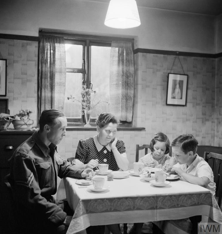 Richard Sainsbury has tea with his wife and two children, Elaine (6) and David (7). He is dressed in his Home Guard uniform and will be out on duty as soon as he has finished eating.