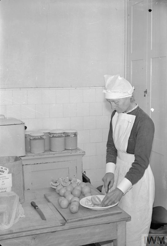 A cook at the Chaim Weizmann Home at Tapley Park, Instow, Devon, cuts oranges for the children. Oranges were scarce during the Second World War and priority for this fruit was given to children over adults. When oranges weren't available, orange juice and blackcurrant puree provided an alternative source of vitamin C.