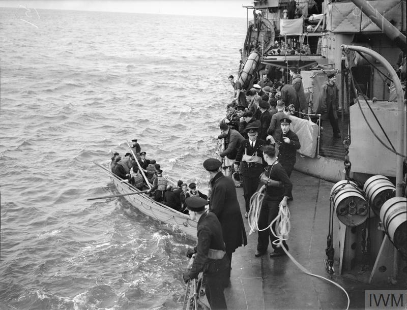 HMS KELVIN RESCUES ESCAPED PRISONERS OF WAR, ENDING FIVE MONTHS OF THRILLS AND ADVENTURES. DECEMBER 1940, ON BOARD HMS KELVIN. EIGHTEEN MEN STANDING ON THE DECK OF A NEUTRAL CARGO BOAT, CHEERED THE KELVIN AS IT CAME TO RESCUE THEM, AND END FIVE MONTHS OF ADVENTURES FOR THIRTEEN OF THE EIGHTEEN RESCUED MEN. THE THIRTEEN WERE MEMBERS OF THE 51ST HIGHLAND DIVISION WHO WERE CAPTURED IN JUNE 1940 DURING THE GERMAN ADVANCE ON THE SOMME. ONE NIGHT HEADED BY THEIR MAJOR, THEY ESCAPED, EVENTUALLY REACHING VICHY WHERE THEY SOMEHOW MANAGED TO OBTAIN FRENCH MILITARY UNIFORMS. FROM VICHY THEY MADE THEIR WAY TO THE SOUTH OF FRANCE, WHERE THEY OBTAINED UNIFORMS OF THE FOREIGN LEGION, TOGETHER WITH FORGED PAPERS, AND GOT TO MOROCCO WHERE THEY WERE INTERNED. THEY ESCAPED AGAIN, REACHING CASABLANCA, WHERE THEY SLIPPED ABOARD THE PORTUGUESE CARGO VESSEL. ONCE AT SEA THEY DECLARED THEMSELVES TO THE SKIPPER, THE SHIP CONTINUED ON ITS JOURNEY TO PORTUGAL DESPITE THIS. FIFTEEN MILES OUT HMS KELVIN ARRIVED AT THE SCENE AND DECIDED TO INVESTIGATE THE SHIP, AND TOOK THE MEN OFF ALONG WITH TWO FRENCHMEN ON THEIR WAY TO JOIN GENERAL DE GAULLE'S FREE FRENCH ARMY, TWO BRITISH AIRMEN, AND ONE AUSTRIAN REFUGEE.