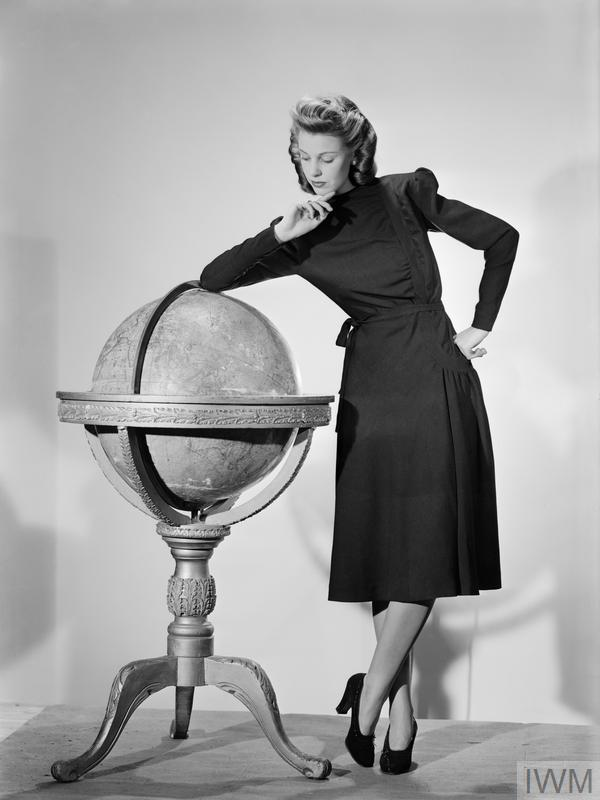 A model leans on a large globe as she shows off her black woollen Utility Atrima dress, costing 11 coupons.