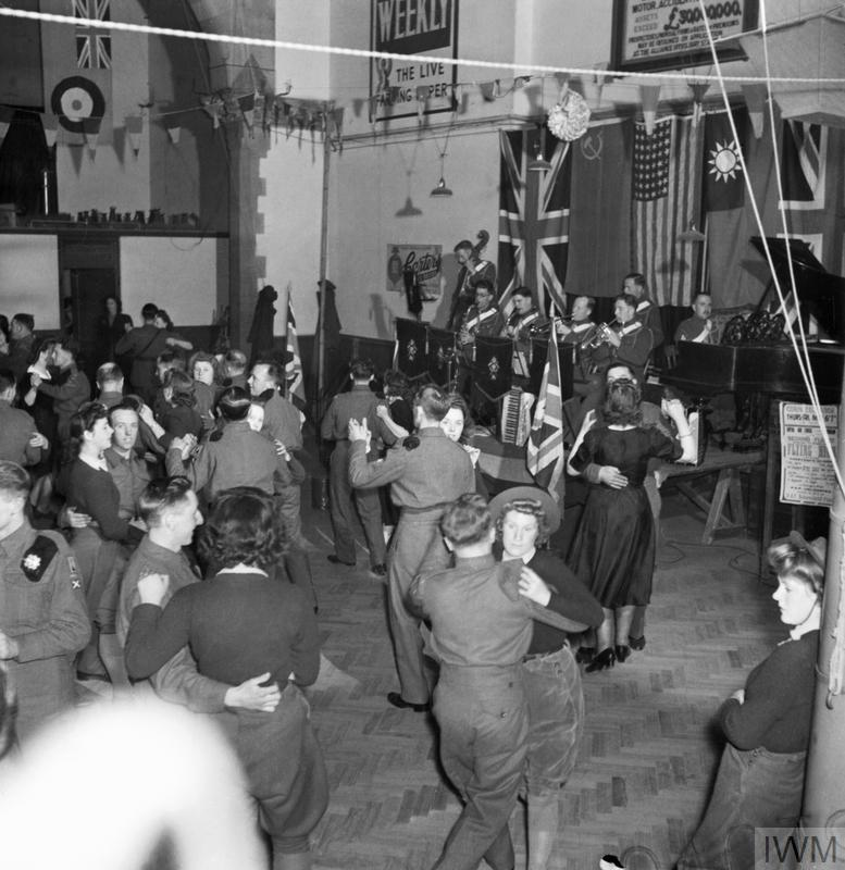 Land Girls, some in uniform, some in mufti, dance with British soldiers at a dance in a large hall, near to their camp in Culford, Suffolk.