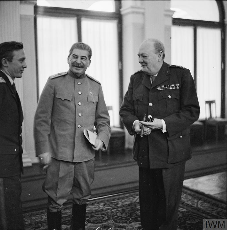 Winston Churchill shares a joke with Marshal Stalin (with the help of Pavlov, Stalin's interpreter, left) in the conference room at Livadia Palace during the Yalta Conference.