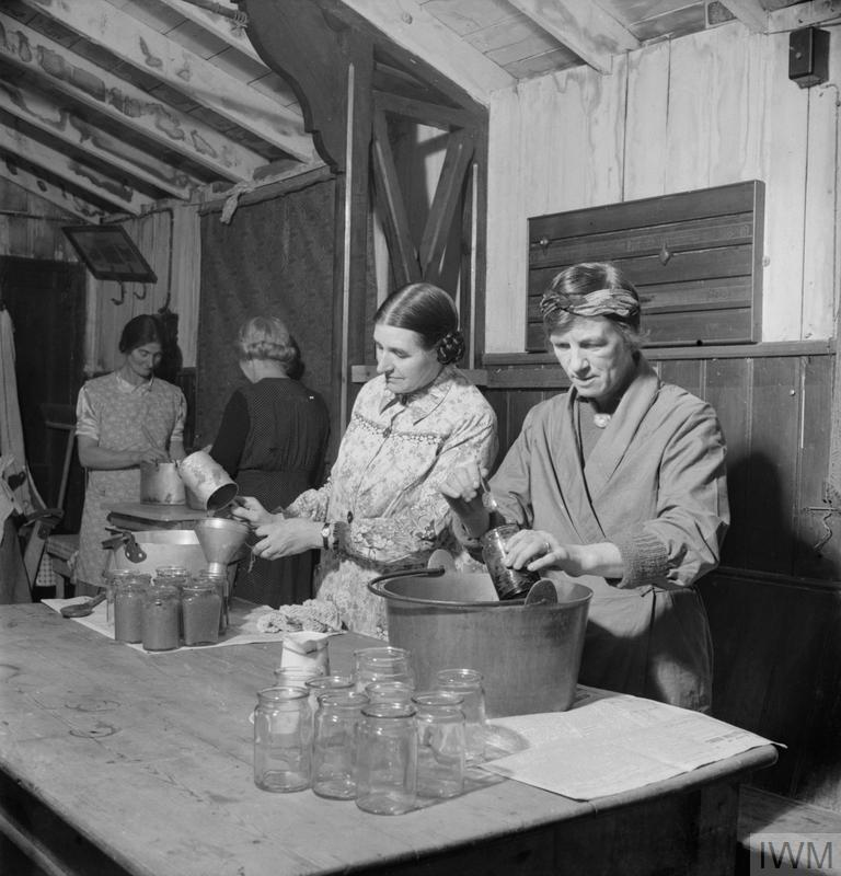 Women's Institute members Mrs Randall (left foreground) and Mrs Dodd (right foreground) bottle jam in the Peace Hall (an army hut converted into a village hall) at Rowney Green, Worcestershire. The fruit was provided by people in the village, from their own gardens, and the sugar came from the government. According to the original caption, this centre has made nearly a ton and three-quarters of jam in the three seasons since the scheme began. Mrs Randall is the centre organiser.