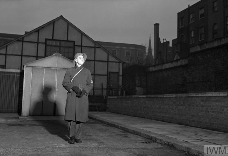 As well as working in a factory and being a member of the Air Training Corps, 19 year old George Metcalfe also spends time as a fire watcher. He is on duty once every ten days, and can be seen here in tin hat and 'Fire Guard' brassard patrolling his 'beat' around Norwood, London.