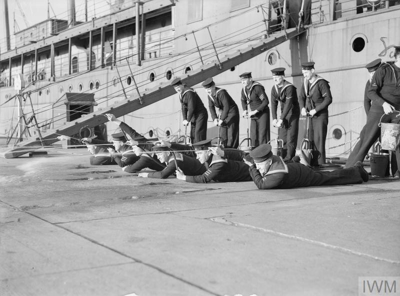 MEN OF THE ROYAL NAVY UNDERGOING TRAINING IN FIRE FIGHTING AT A NAVAL ESTABLISHMENT. 1941, AT HMS PEMBROKE.