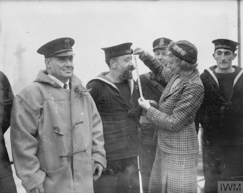 FINDING THE PERFECT SAILOR. 9 DECEMBER 1941, HMS COCHRANE, ROSYTH. MRS HASWELL MILLER (ASSOCIATE ROYAL SCOTTISH ACADEMY) COMMISSIONED TO PRODUCE HISTORIC PAINTINGS TO ILLUSTRATE NAVAL COSTUMES, INTERVIEWING VARIOUS RATINGS.